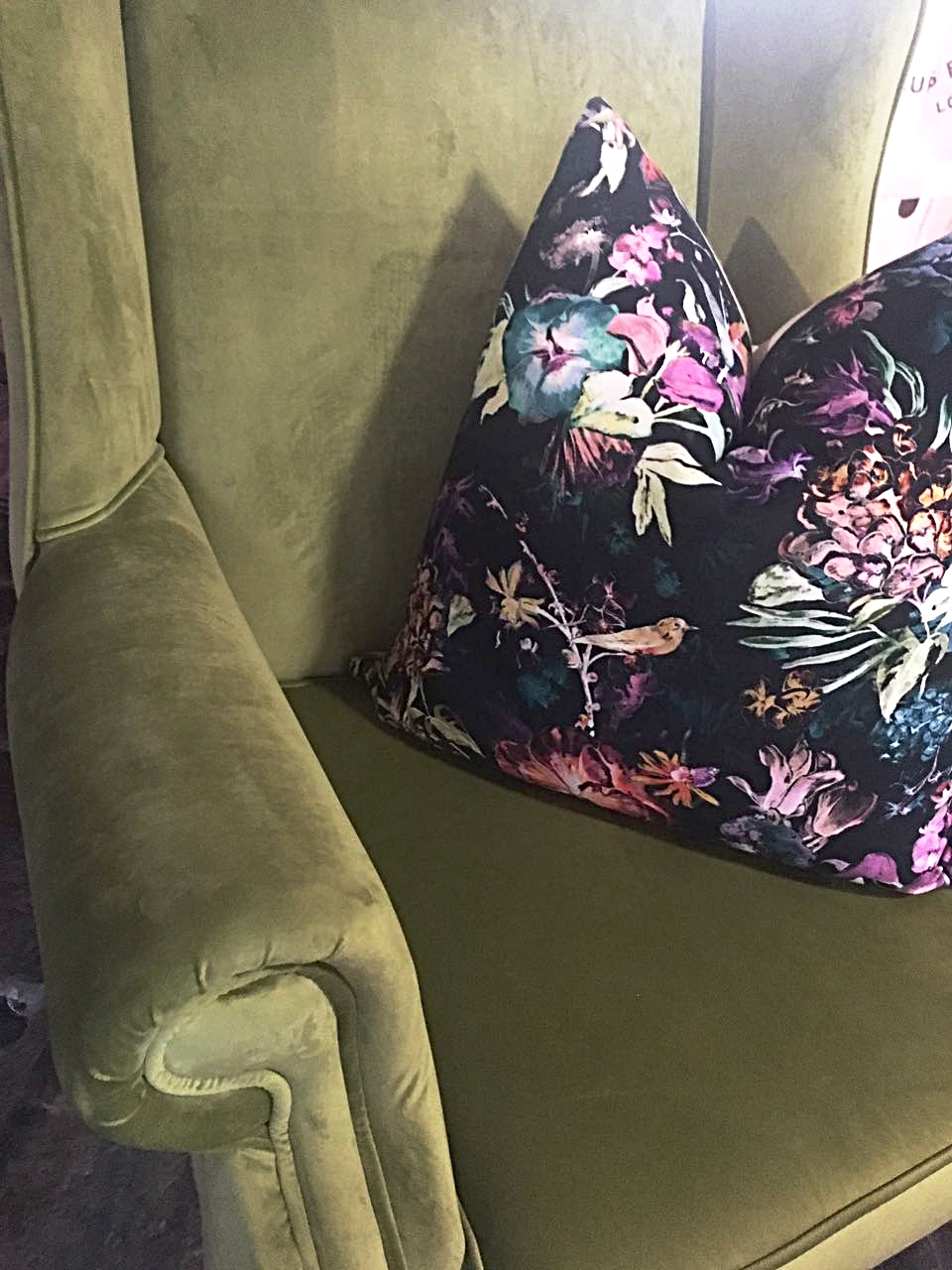 Green velvet wingback chair with tropical floral scatter cushion.