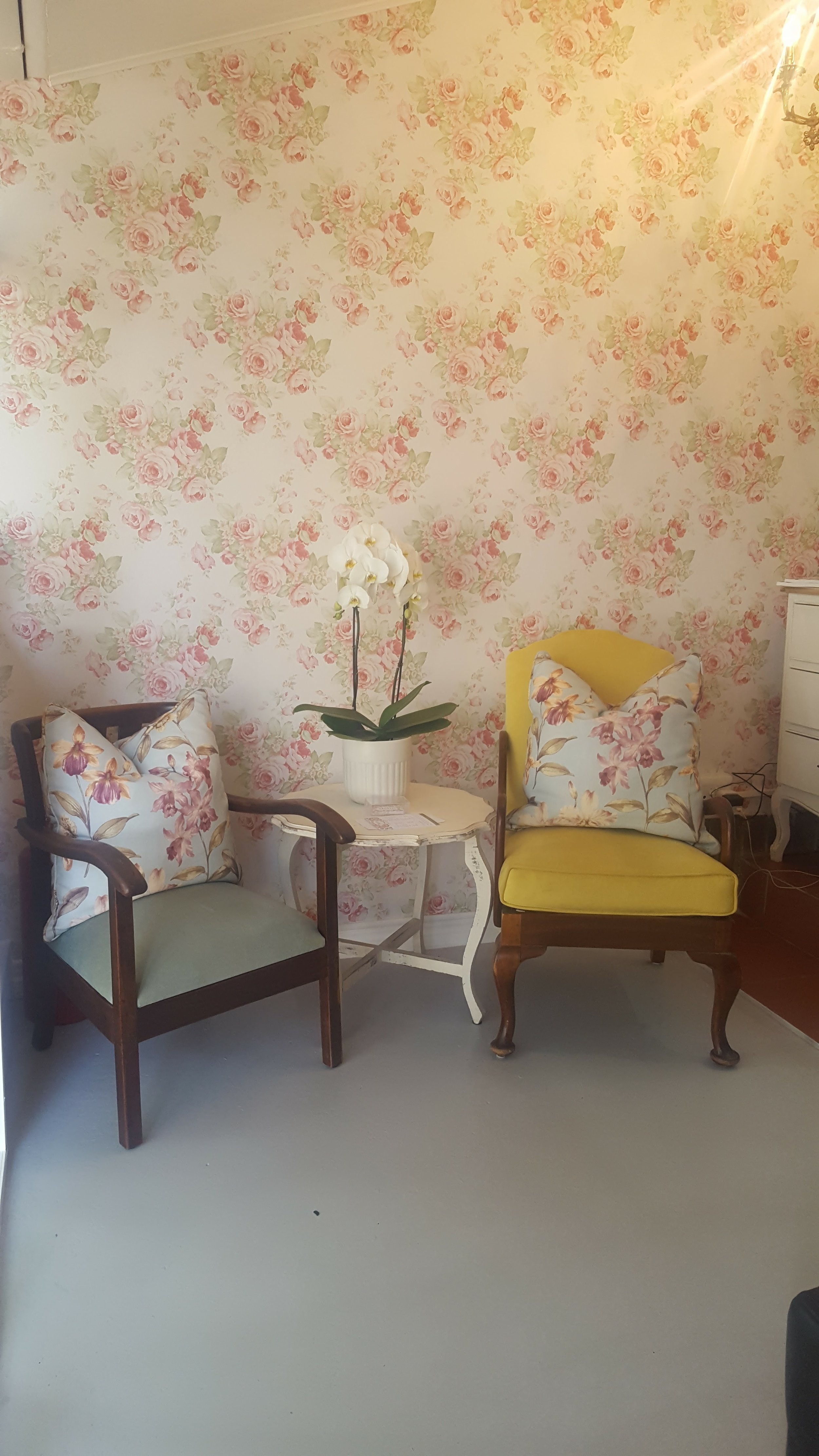 Two green velvet chairs in front of a floral wallpaper