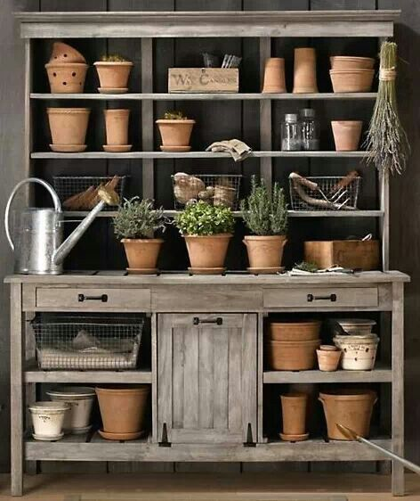 terra cotta pots, gardening tools and seedlings on a potting bench