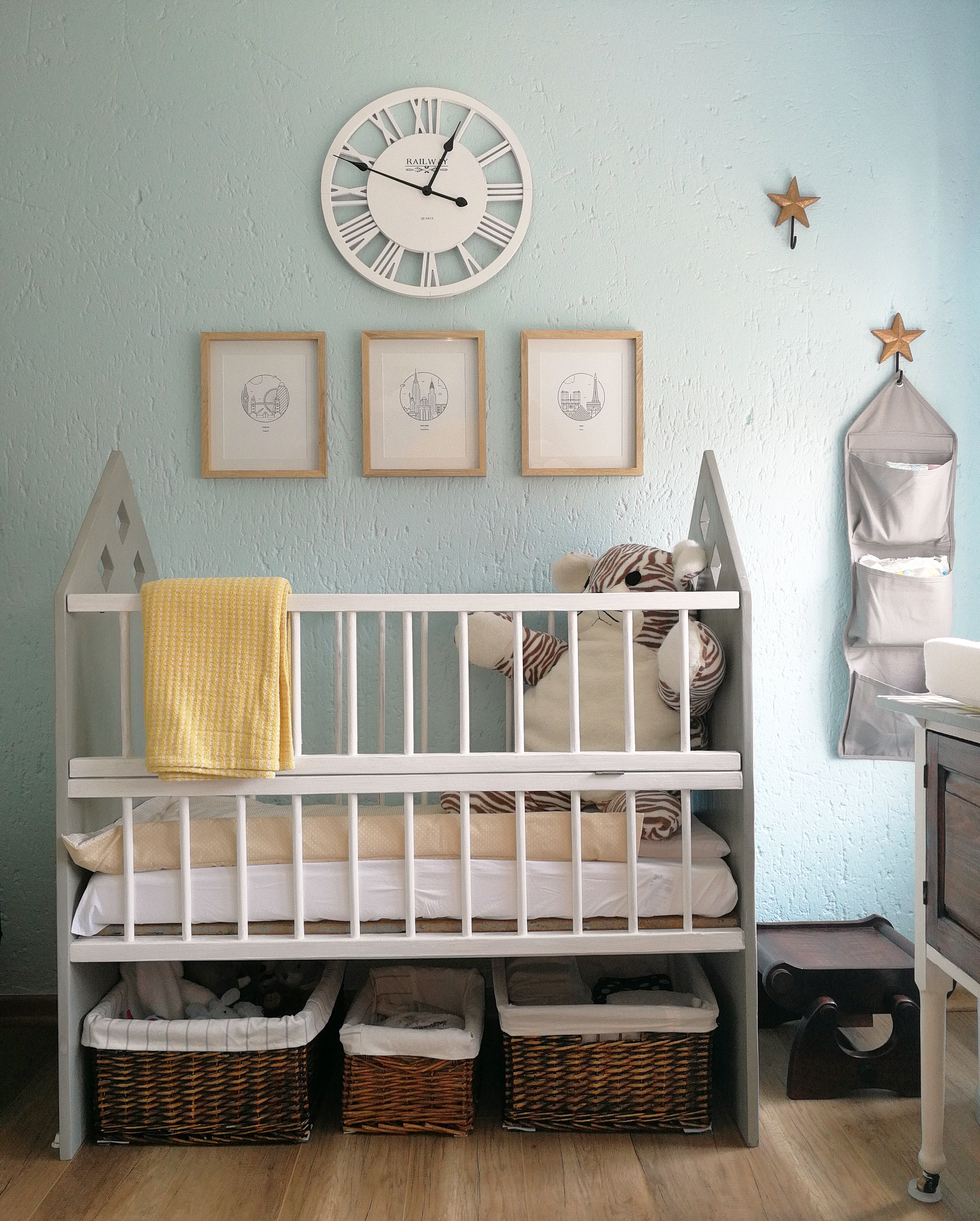 grey and white cot painting in fired earth chalk paint for nursery with travel theme, and white clock and prints of travel New York, Paris, London, designed by Tassels & Tigers Interior Decor and Designer in Johannesburg, South Africa