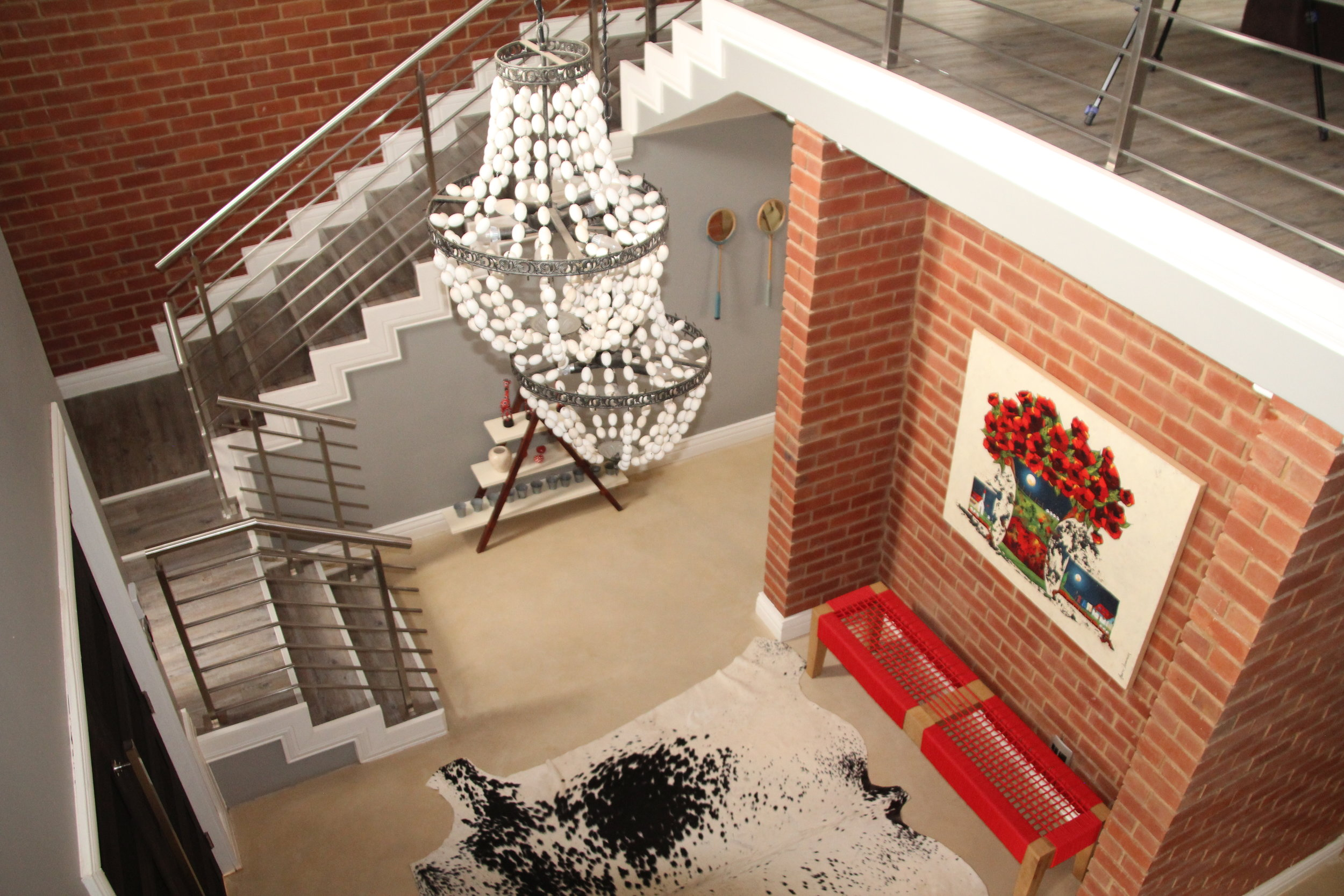 A double storey industrial entrance hall with understated, striking features in red, black and white.