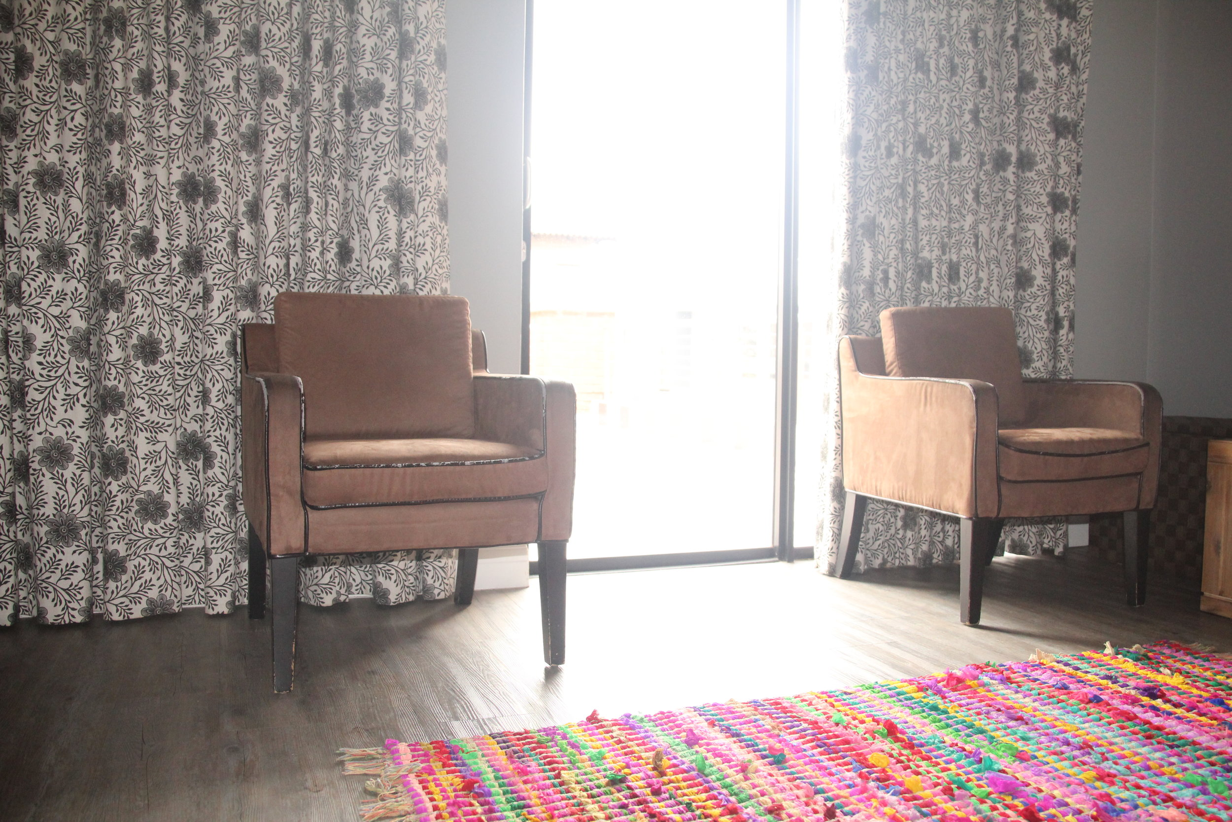 5 Upstairs Pajama Lounge with chairs and curtains with contrast piping and bright rug.JPG