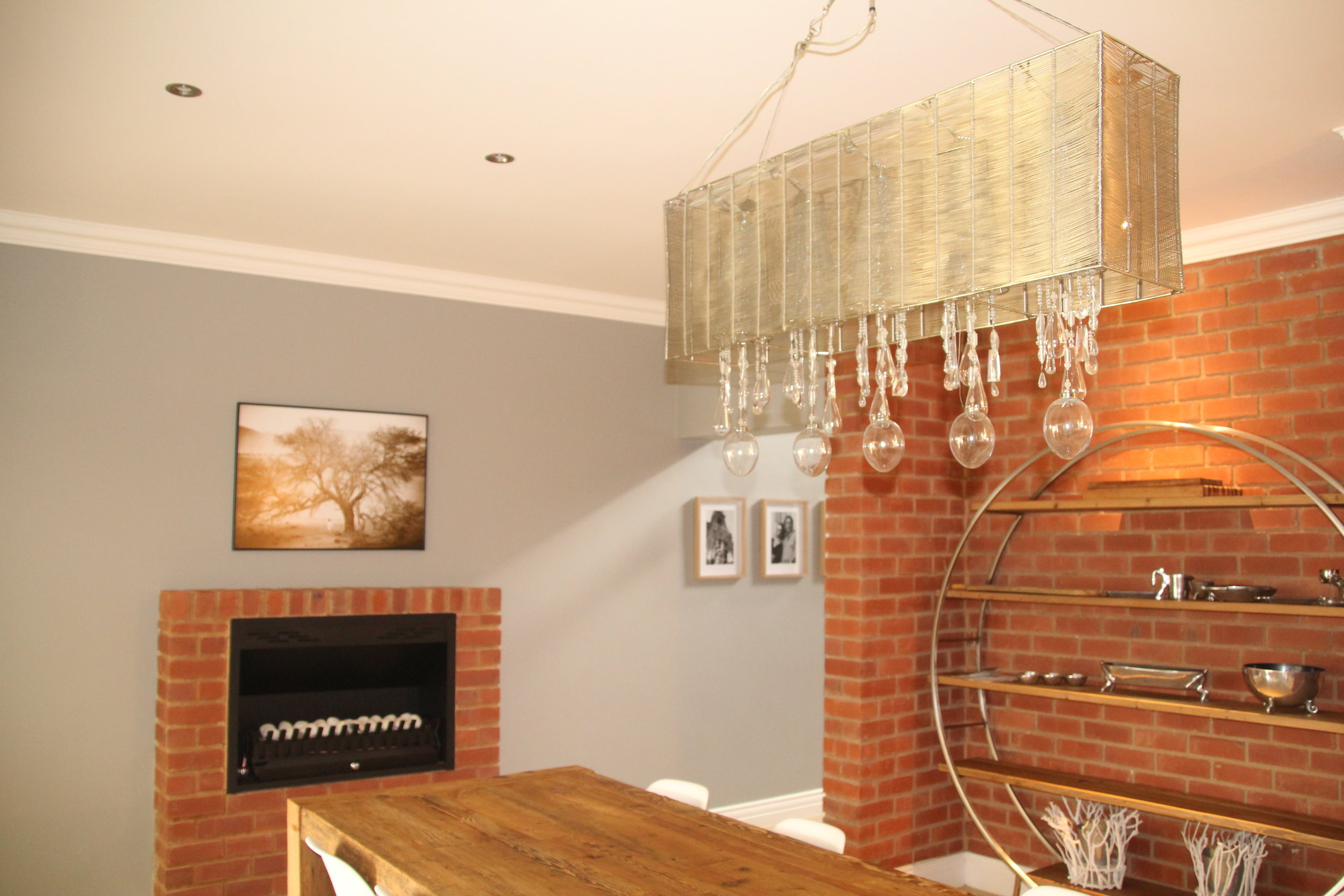 The dining room is seperated from the entrance hall by means of a partition wall while being well integrated with the rest of the open plan living space through a walkway.  Warm brick features and wood contrast beautifully with a wire and crystal chandelier and plastic eames chairs.