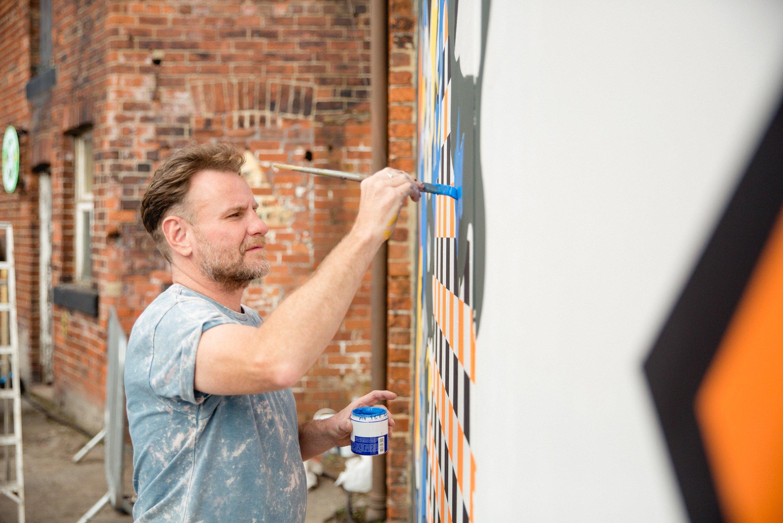 Nicholas Dixon street artist painting at Canal Mills
