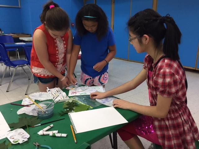 Intern helping kids with paint.JPG
