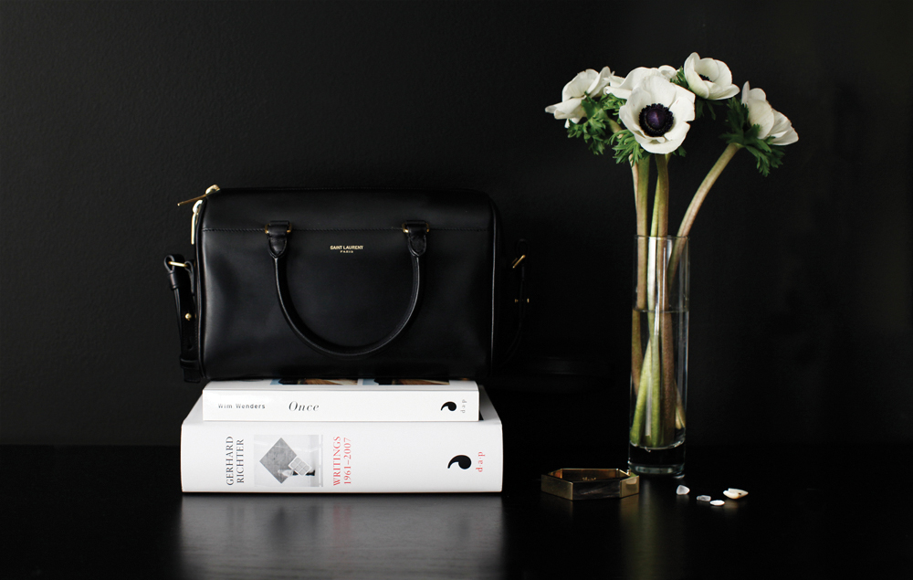 Photo by me, on my bedroom dresser -  Saint Laurent  baby duffle bag the same size as a good book, previous  weekend read  , Céline  bracelet.