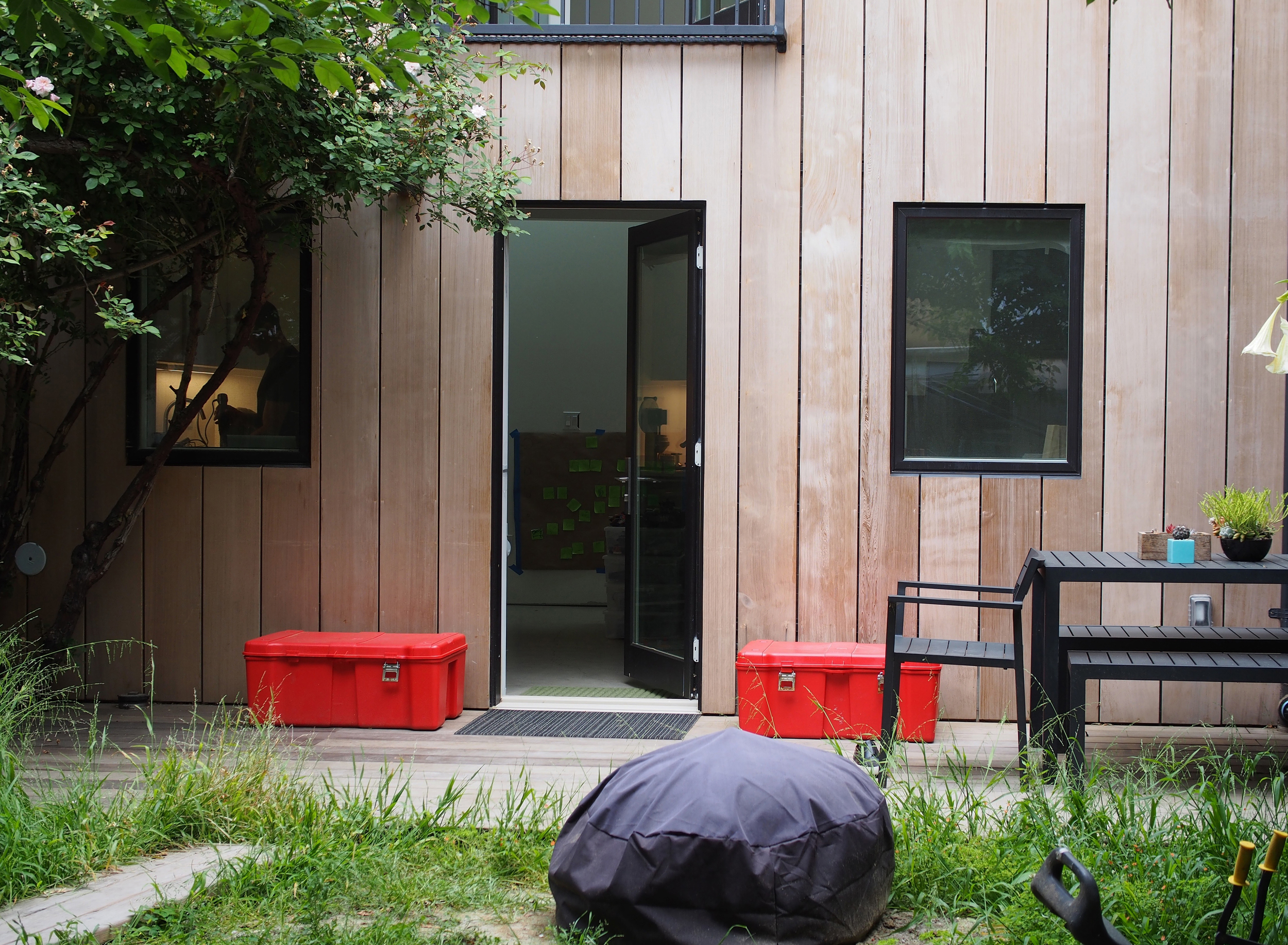 Red storage boxes house the family shoe collection punctuate their outdoor space - a welcome extension to their living area.