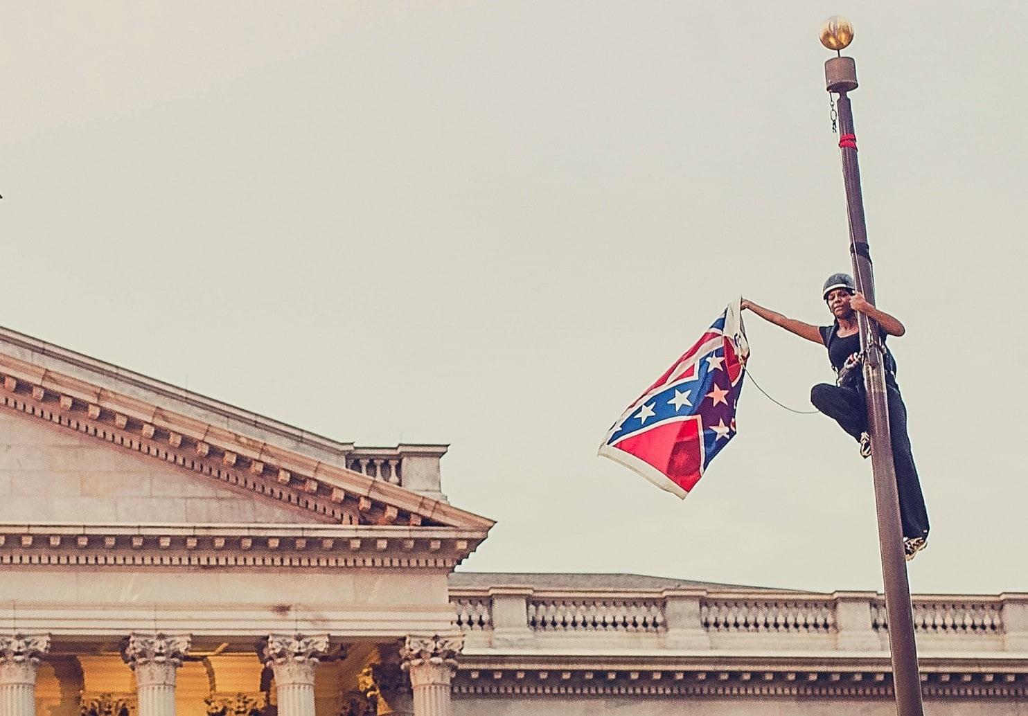 Bree Newsome takes down the Confederate flag from a pole at the Statehouse Grounds in Columbia in 2015.  Image credit: Washington Post