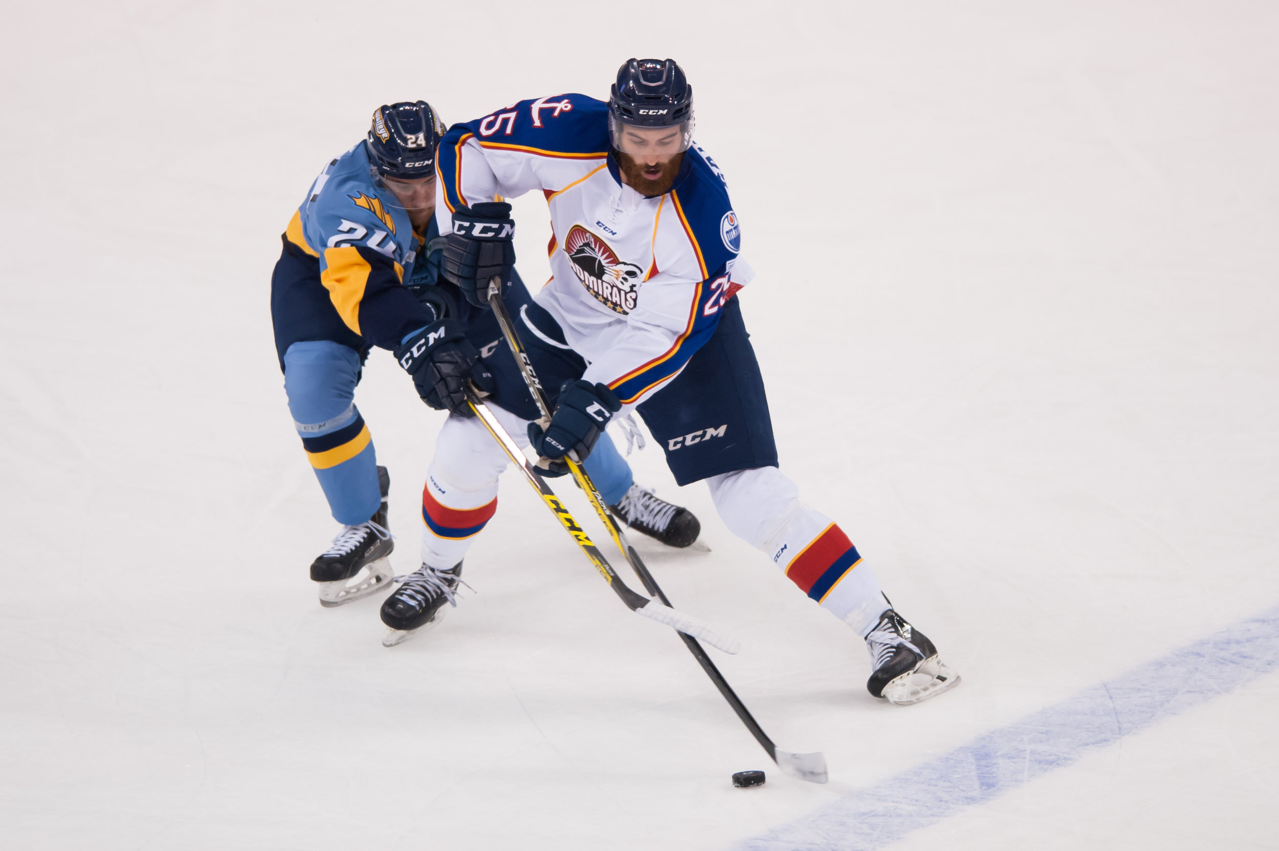 Norfolk Admirals forward Danick Gauthier (25) and Toledo Walleye forward Tylor Spink (24) fight for the puck during Saturday night's game at the Scope Arena in Norfolk, Virginia. Toledo defeated Norfolk 4 to 1.
