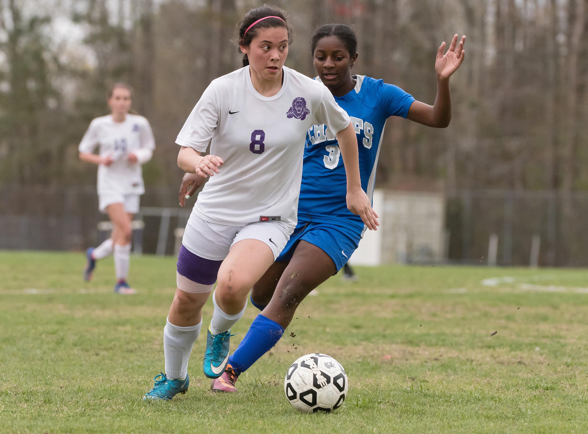 Tallwood defender Adriana Pemberton (8) moves the ball past Kempsville forward Mychael McKeever (3) during Monday night's game at Tallwood High School. Kempsville defeated Tallwood 2-0.