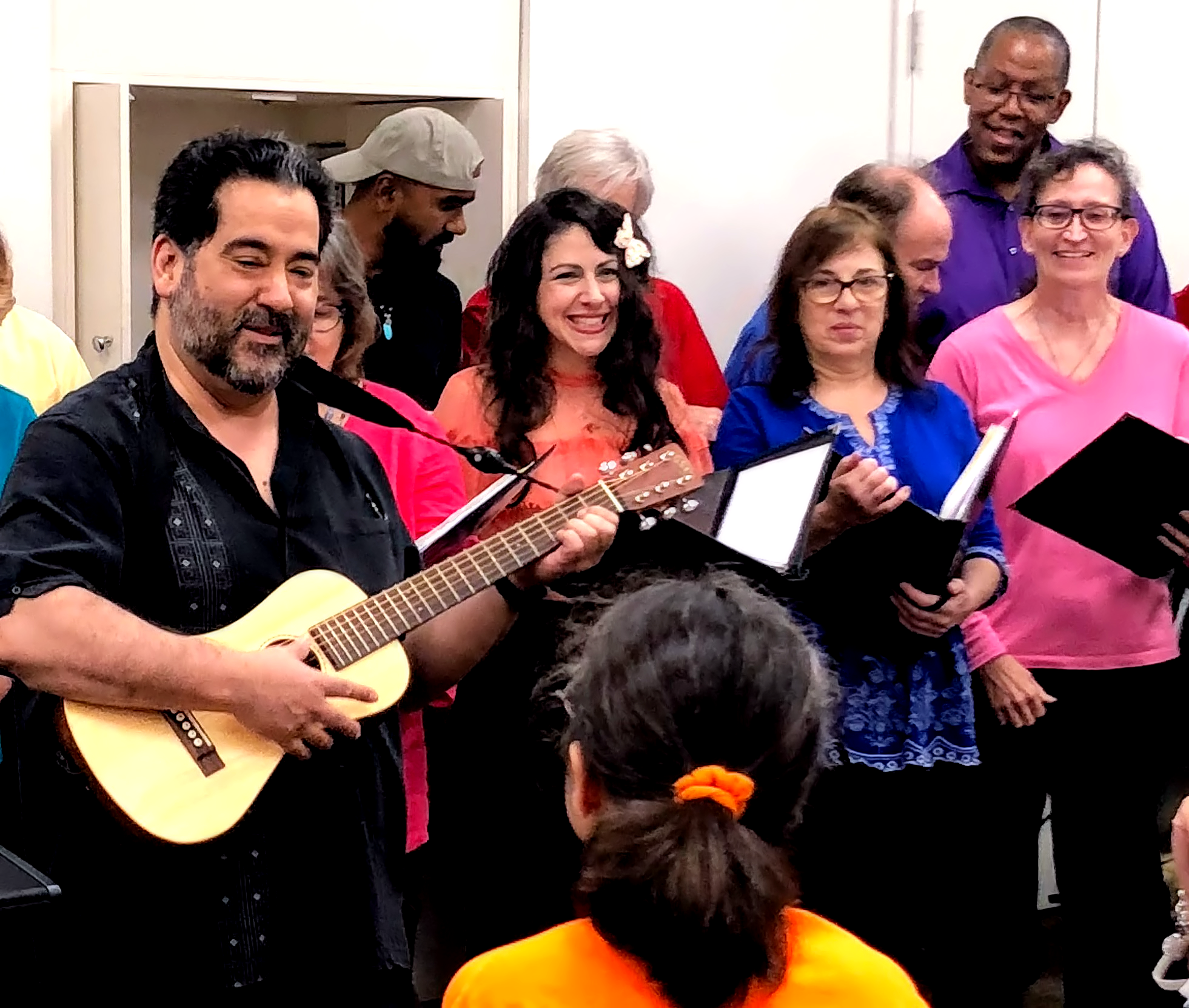 "Choir director René Galván, on guitar, leads the choir in ""Oye Como Va"" at YAI."