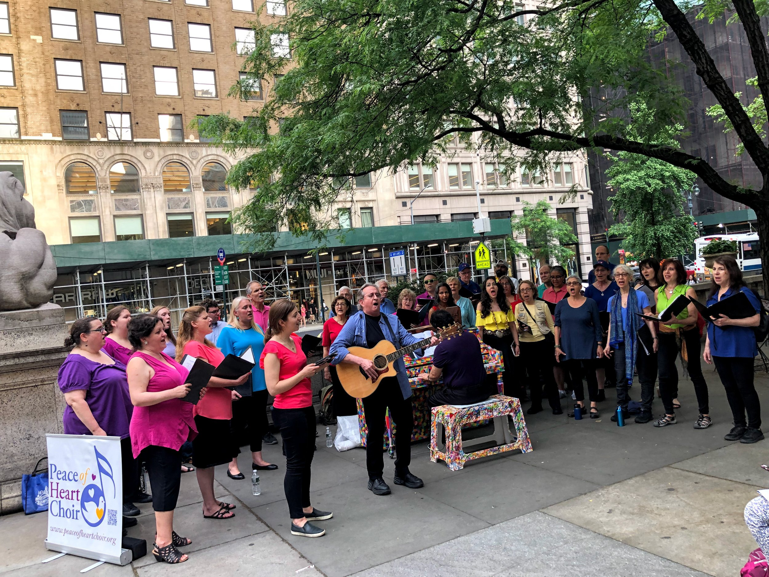 The choir sings near Patience, one of the famed lion statues, outside the NY Public Library on 5th Avenue.