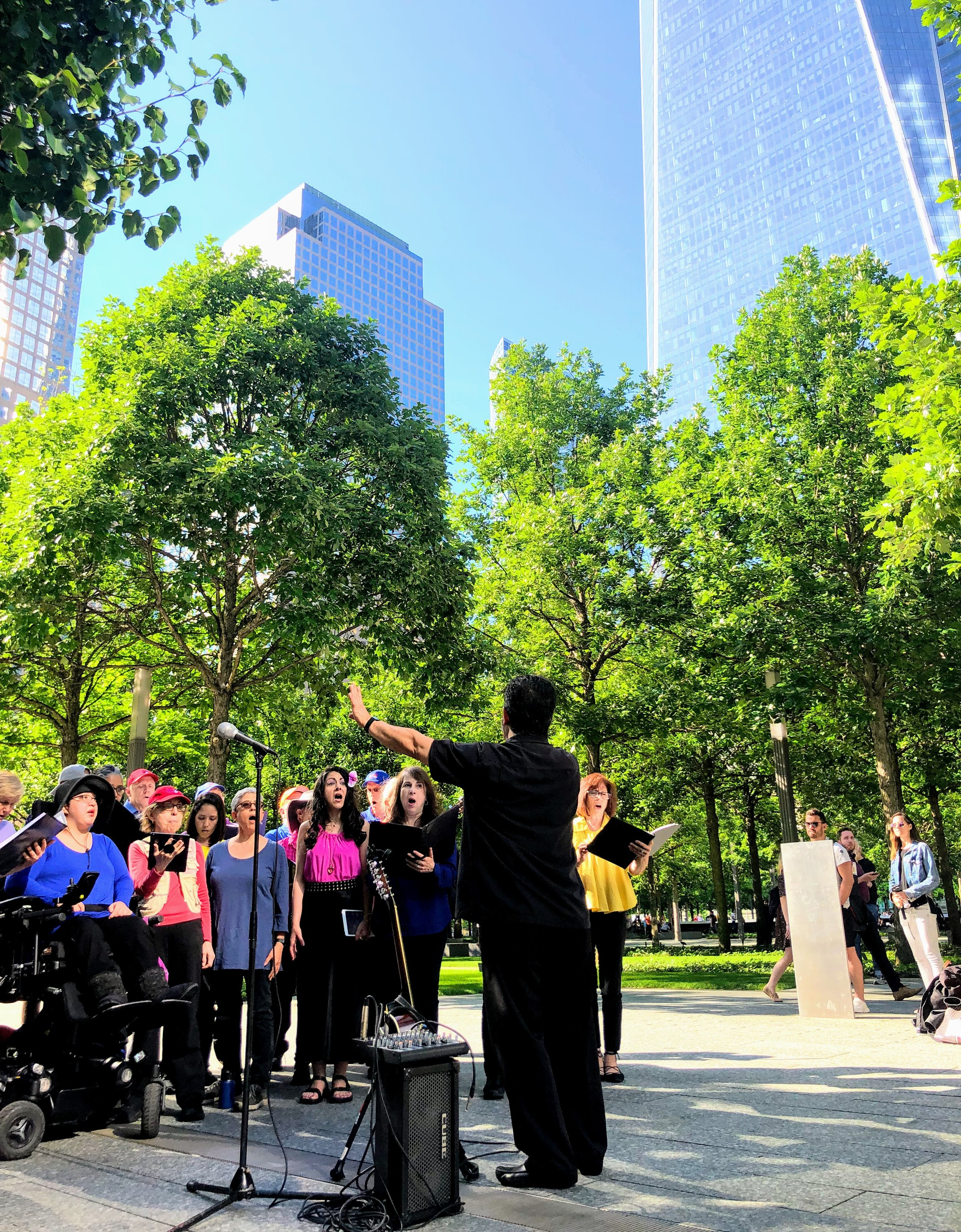 Maestro    René Galván    leads the choir as the Freedom Tower overlooks the choir at the 9/11 Memorial and Museum.