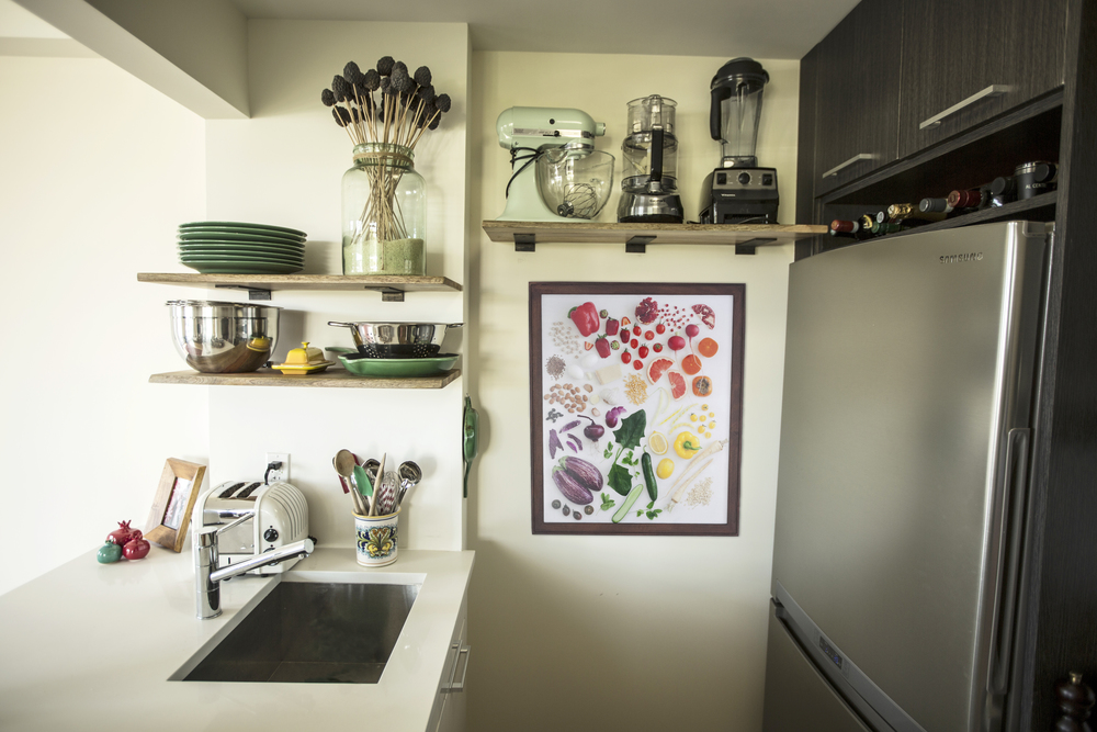 "Holly's ""Colors of the Market"" photographic print is both on a small wall and near a kitchen sink."