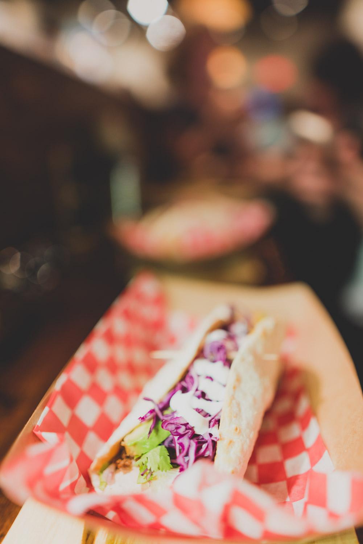 Le tacos est composé tortilla de blé, boeuf haché cuit aux épices mexicaines maison, fromage TexMex, tomates cerises, coriandre, chou rouge, crème sûre à la lime et huile aux piment ancho et poivre chez Deux 22   pour le Carrefour international de théâtre de Québec
