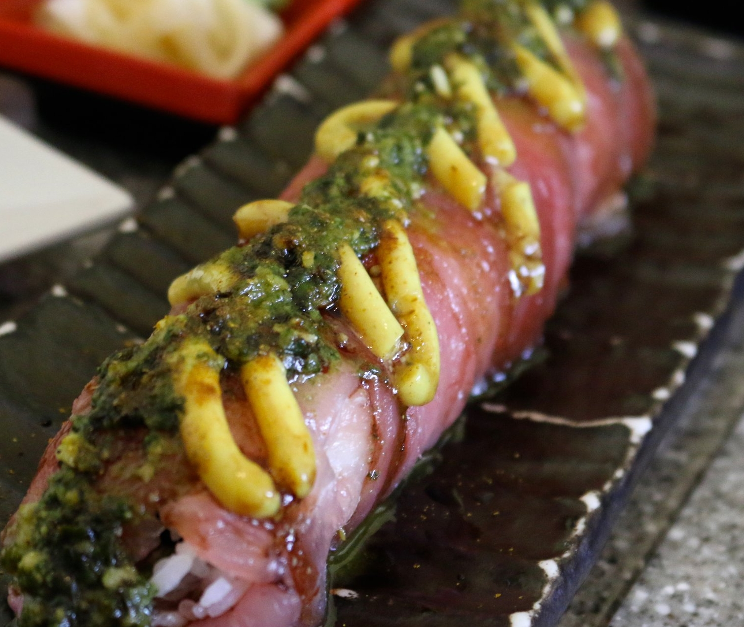 BOMBAY SUNSET ROLL - ahi poke, curry slaw, and Fuji apple wrapped with sashimi of the day