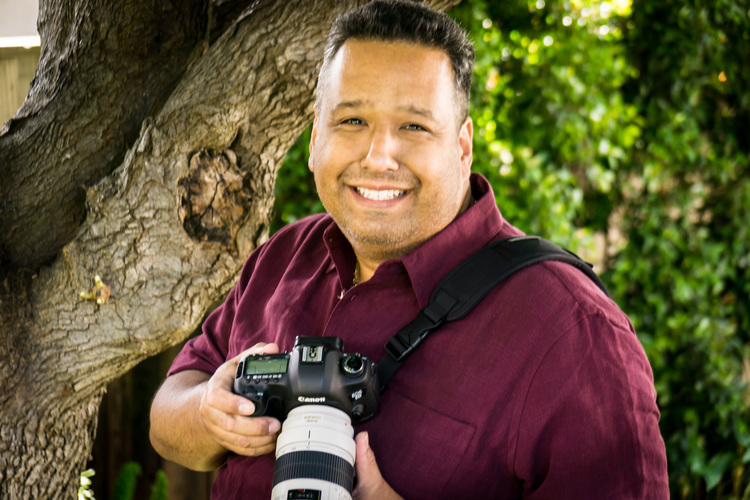 Top Wedding and Portrait Photographer wearing a red shirt, smiling, holding a DSLR Camera