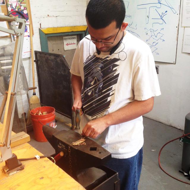 Felix hammering metal at the Steel Yard