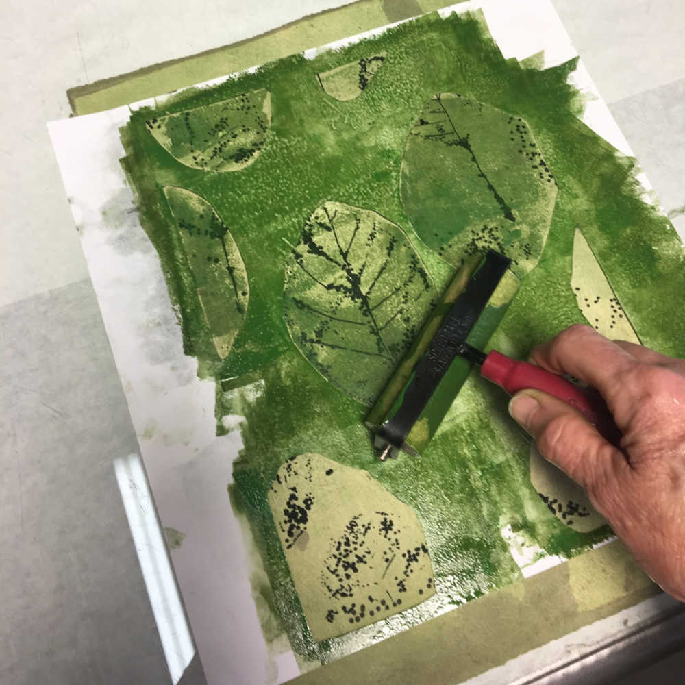 Rolling on another layer of green through a paper mask.