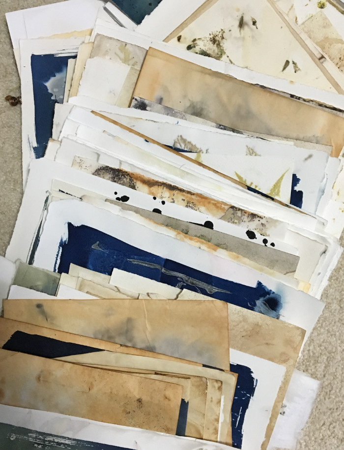 Pile of cyanotype, rusted, and eco-printed papers ready to be turned into original pieces of art by artist Carol Ann Webster