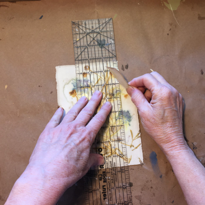 Tearing the paper to fit on the board artist Carol Ann Webster