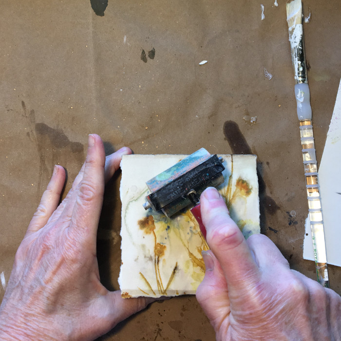 Use a brayer to press down paper on board artist Carol Ann Webster
