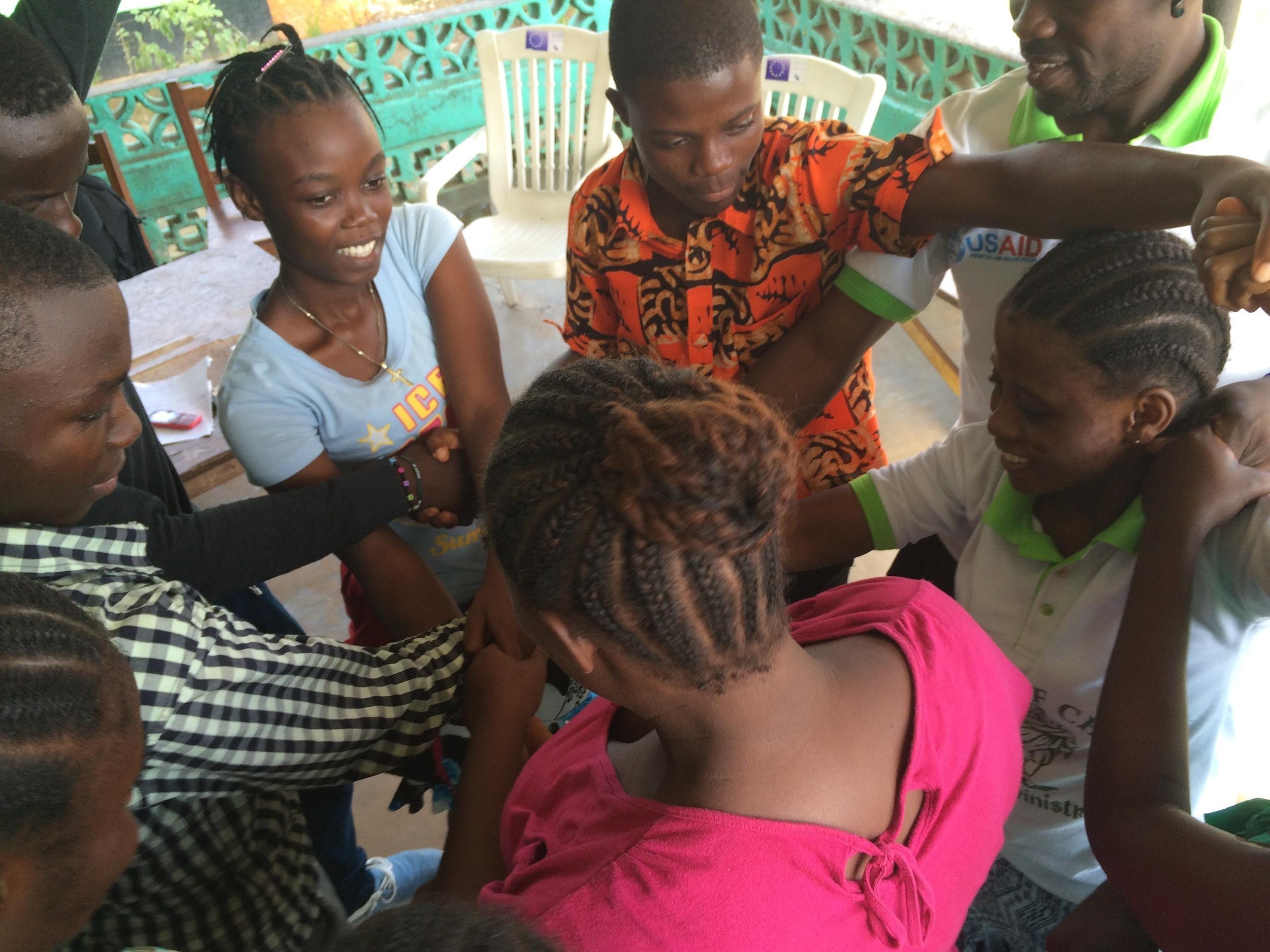 Monrovia scholarship recipients playing leadership games at a meeting.