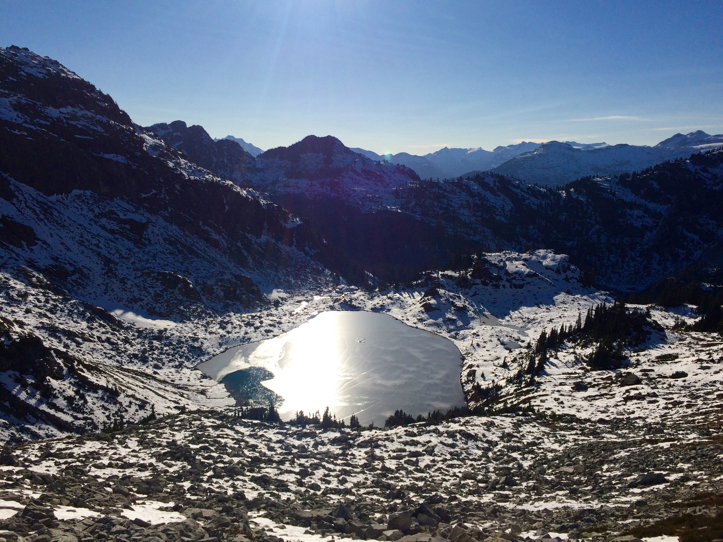 """Looking back across that same lake as we hiked a bit further - at this point, the """"trail"""" was mostly frozen snow and loose rock."""
