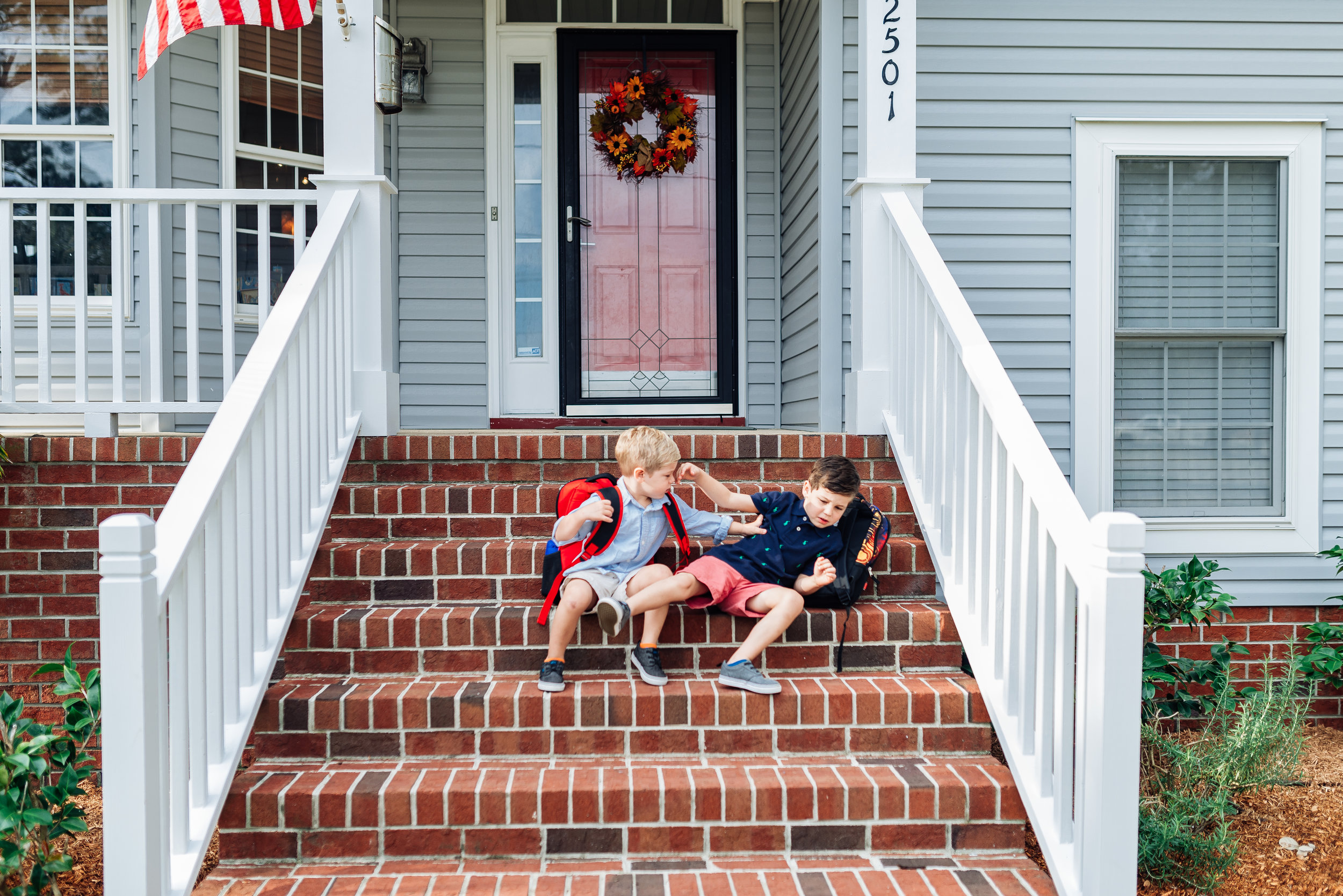 """My kids killing each other (like usual) on our front steps of our old house as I tried to snap a """"nice first day of school photo"""" of them."""