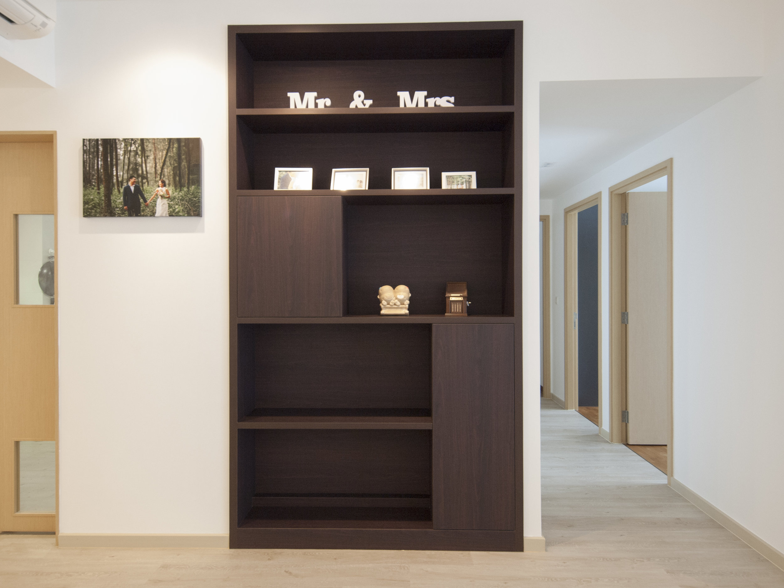 A large space was originally designated for the DB Box and modem.  To optimise the use of space, this was transformed into a shelving cabinet for storage and display, concealing a good amount of electrical trunking and other electrical components while acting as a feature piece.