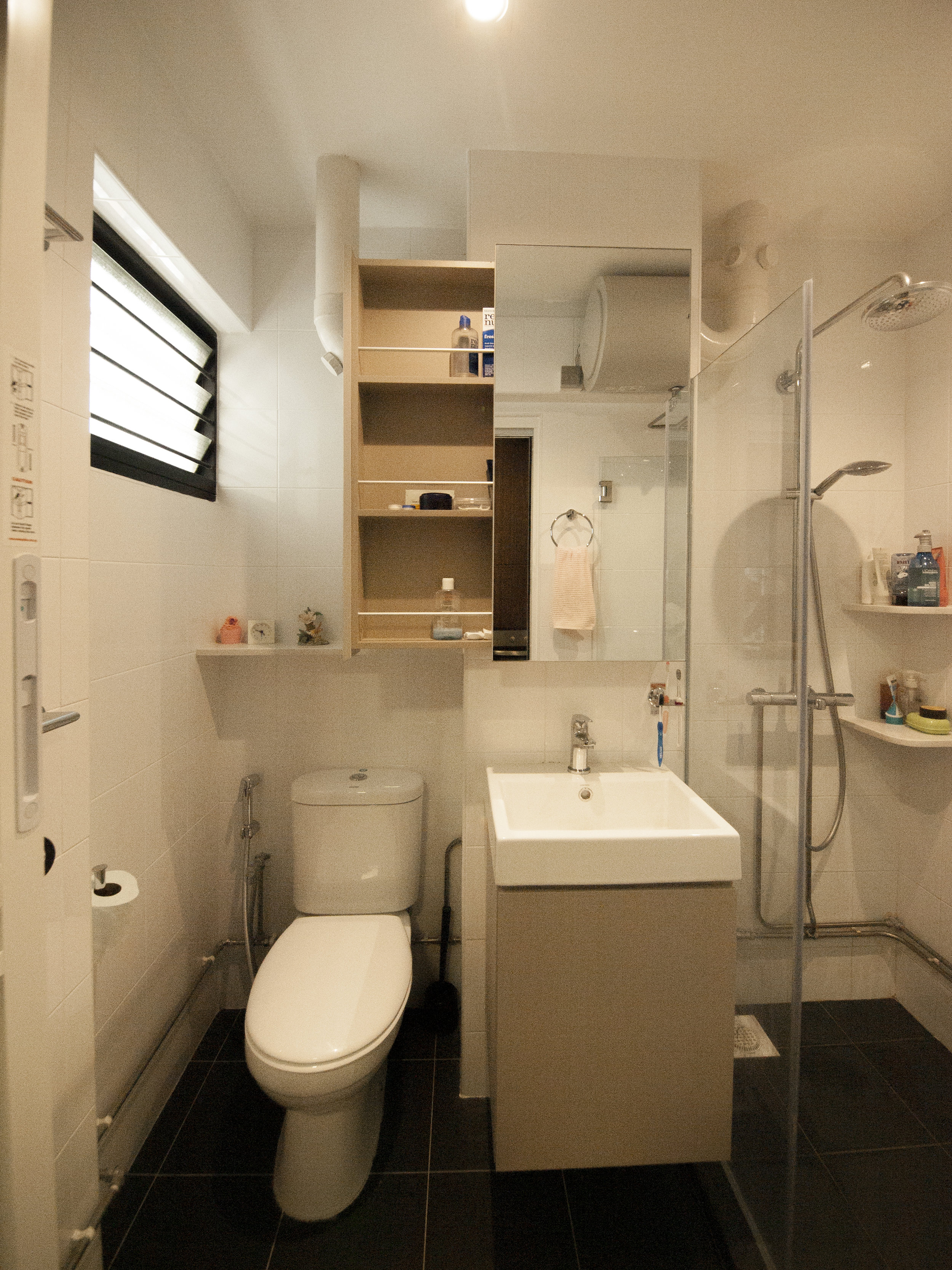 Concealed the floor to ceiling pipes partially to maximise the space and give a clean look. A sliding mirror cabinet allows you to use the mirror while accessing your bathroom essentials!