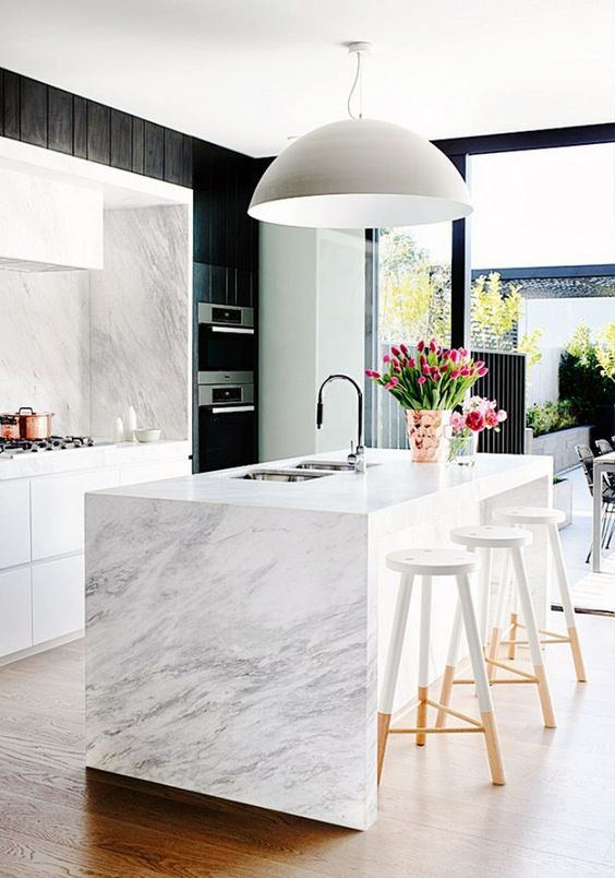 This modern kitchen makes use of marble wallpaper as a clever accent, creating the illusion of marble on the backsplash and walls.