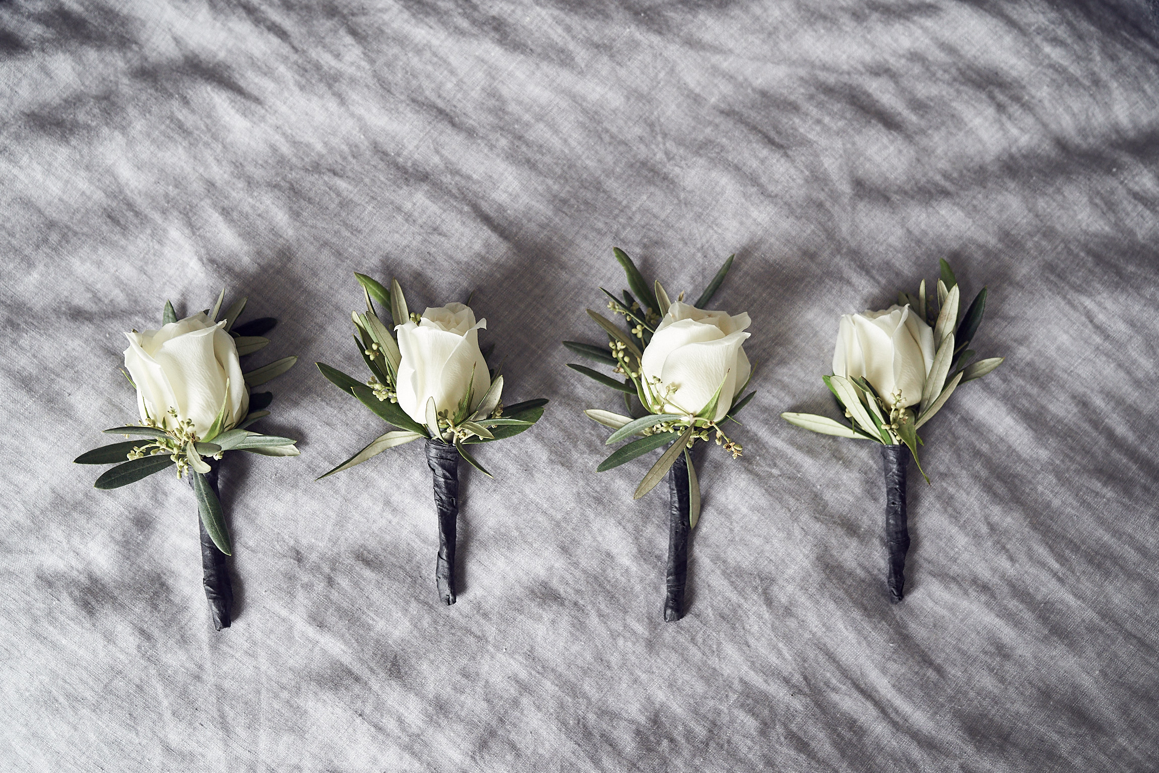 Boutonnieres of white rose bud and dwarf olive leaves