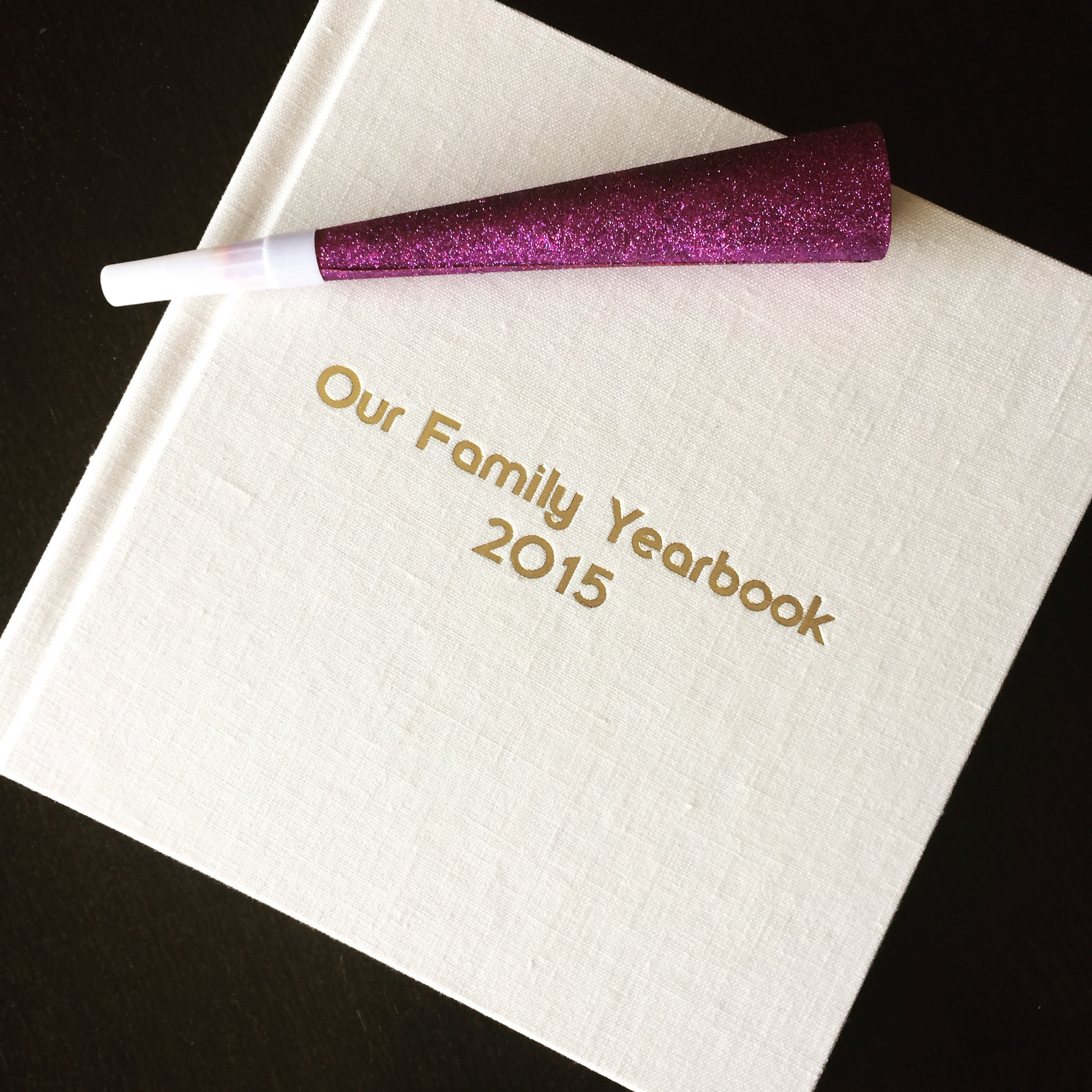 "Capture your family's year in a stunning keepsake. | 10"" x 10"" Signature Album. Linen cover in ""tusk"" with gold debossed lettering."