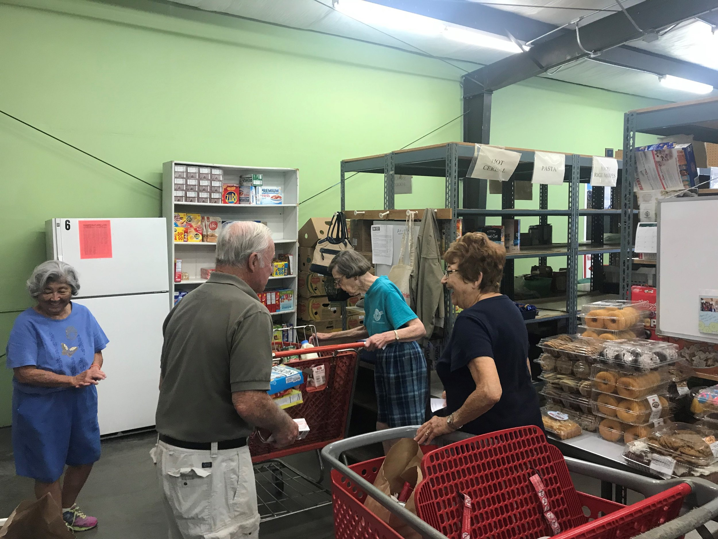 Volunteer shoppers cruise the food aisles selecting items for families.