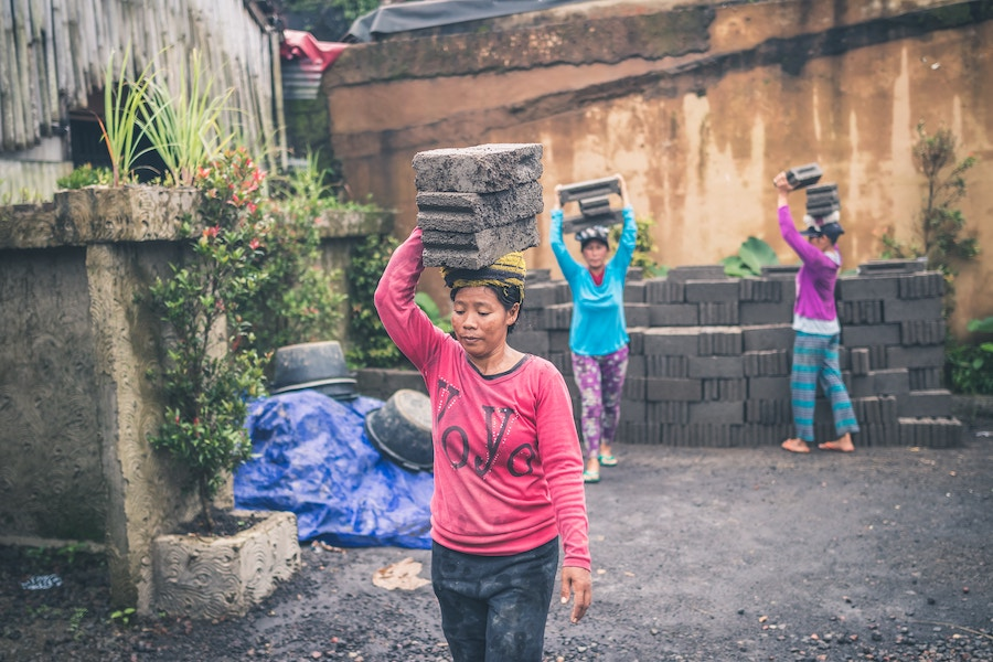 Women in Bali carrying bricks on their heads. Photo courtesy  Artem Bali .