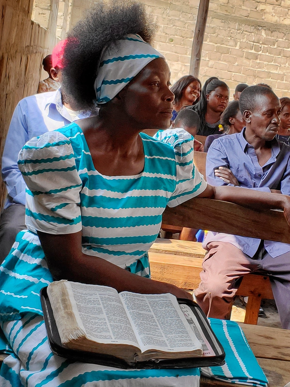 Mrs. Mundia, the mother of new vine founder, yuyi mundia, and the vineyard congregation listen raptly to abby's teaching.