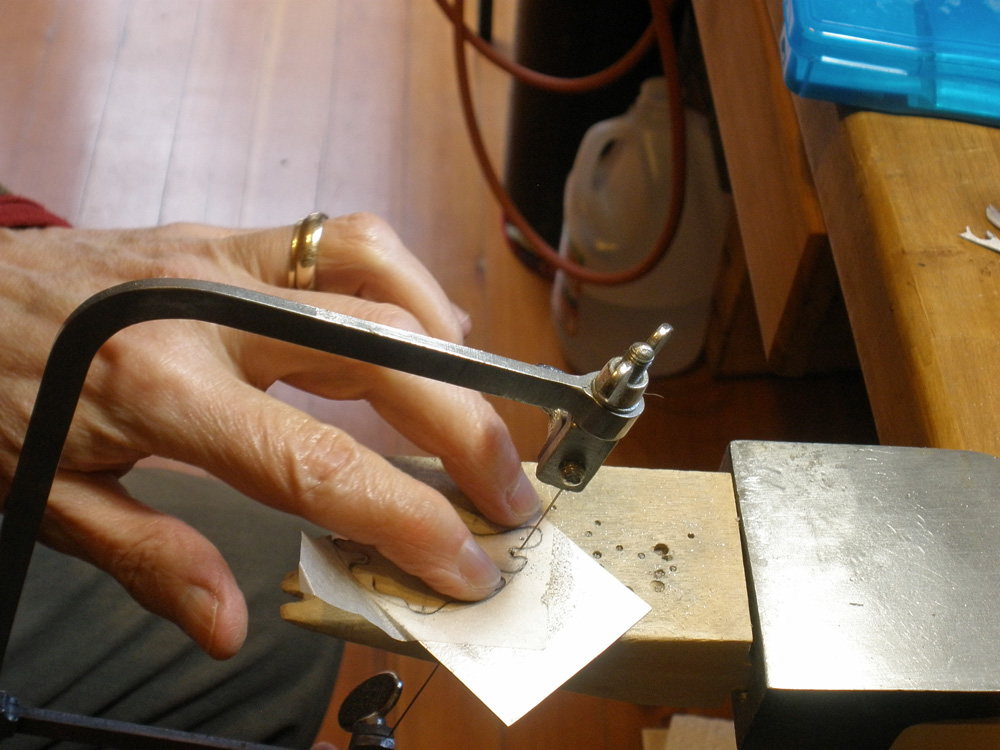 Sawing and piercing out the shapes in the textured sterling
