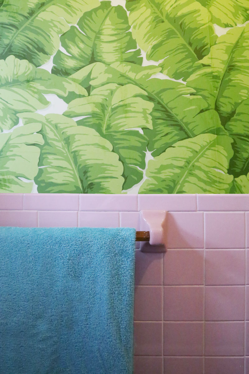 Bright colors make this bathroom just as cheerful as the rest of the house. Patterned foliage wallpaper emphasizes the deep love for plants, clearly, a theme throughout the apartment.