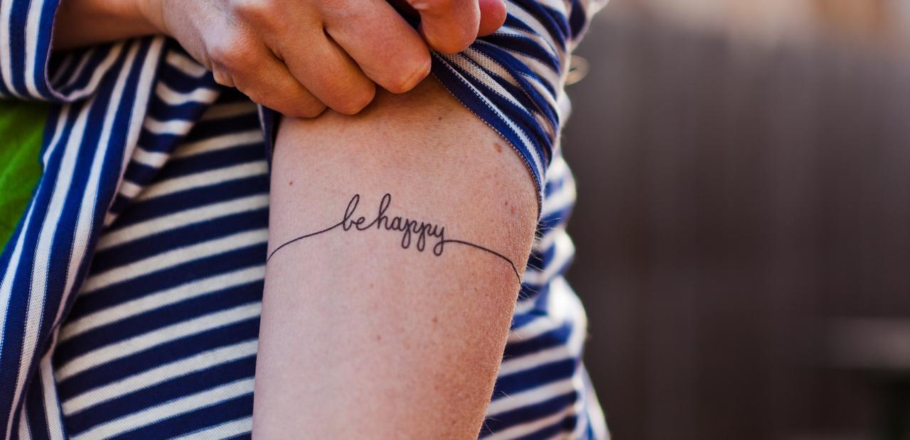 be happy arm tattoo
