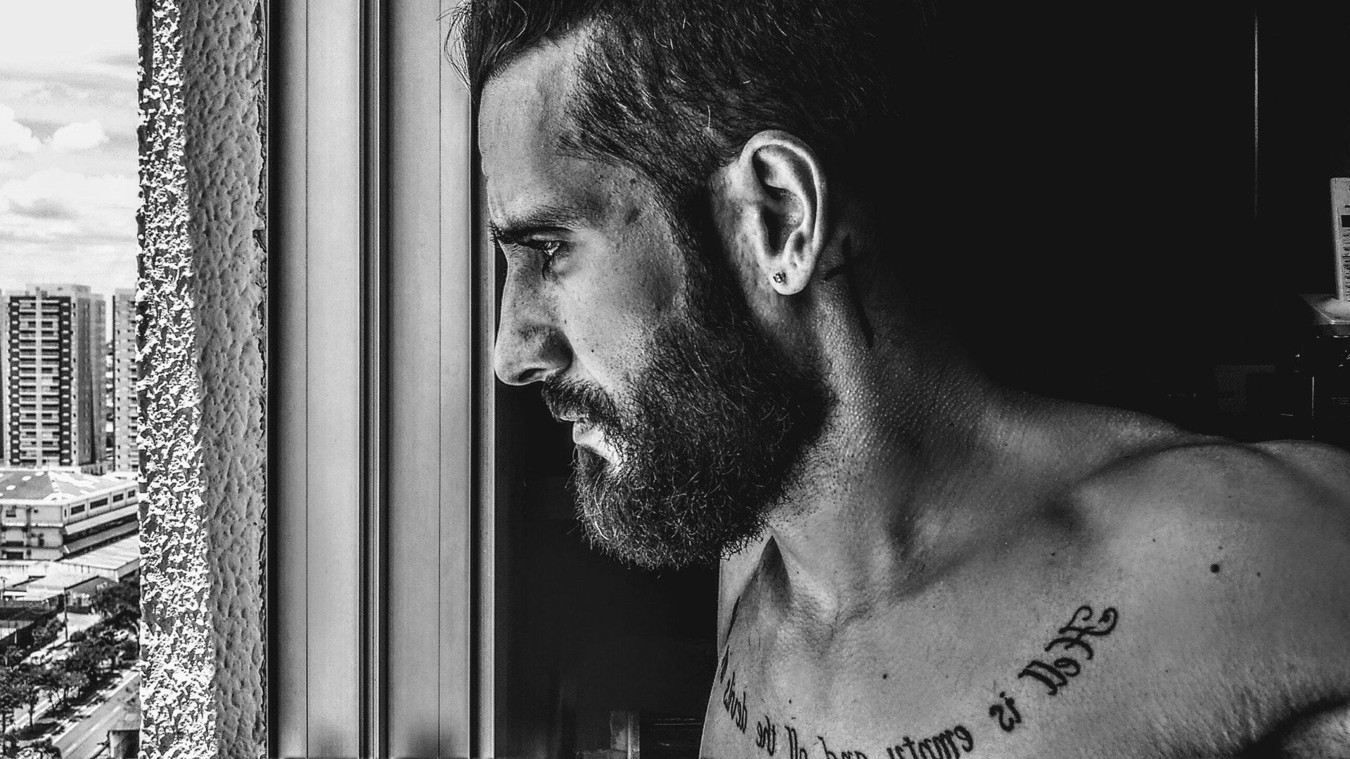 thinking man with tattoo