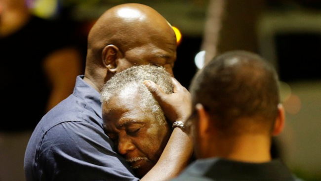 Worshippers embrace following a group prayer across the street from the scene of a shooting at Emanuel AME Church, Wednesday, June 17, 2015, in Charleston, S.C. A white man opened fire during a prayer meeting inside the historic black church, killing multiple people, including the pastor, in an assault that authorities described as a hate crime. (AP Photo/David Goldman)