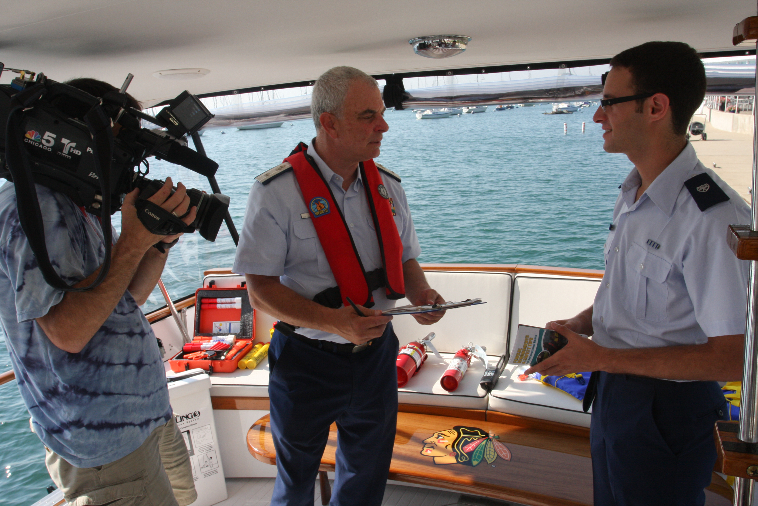 """Roth talks with past District 9WR Commodore Randy Podolsky and a news cameraman on the yacht """"Blackhawk"""" at Monroe Harbor in Chicago, July 19, 2013. Earlier, Commodore Podolsky emphasized the Auxiliary's boating safety mission on live television. Roth assisted with the media event. U.S. Coast Guard photo by Chief Petty Officer Alan Haraf."""