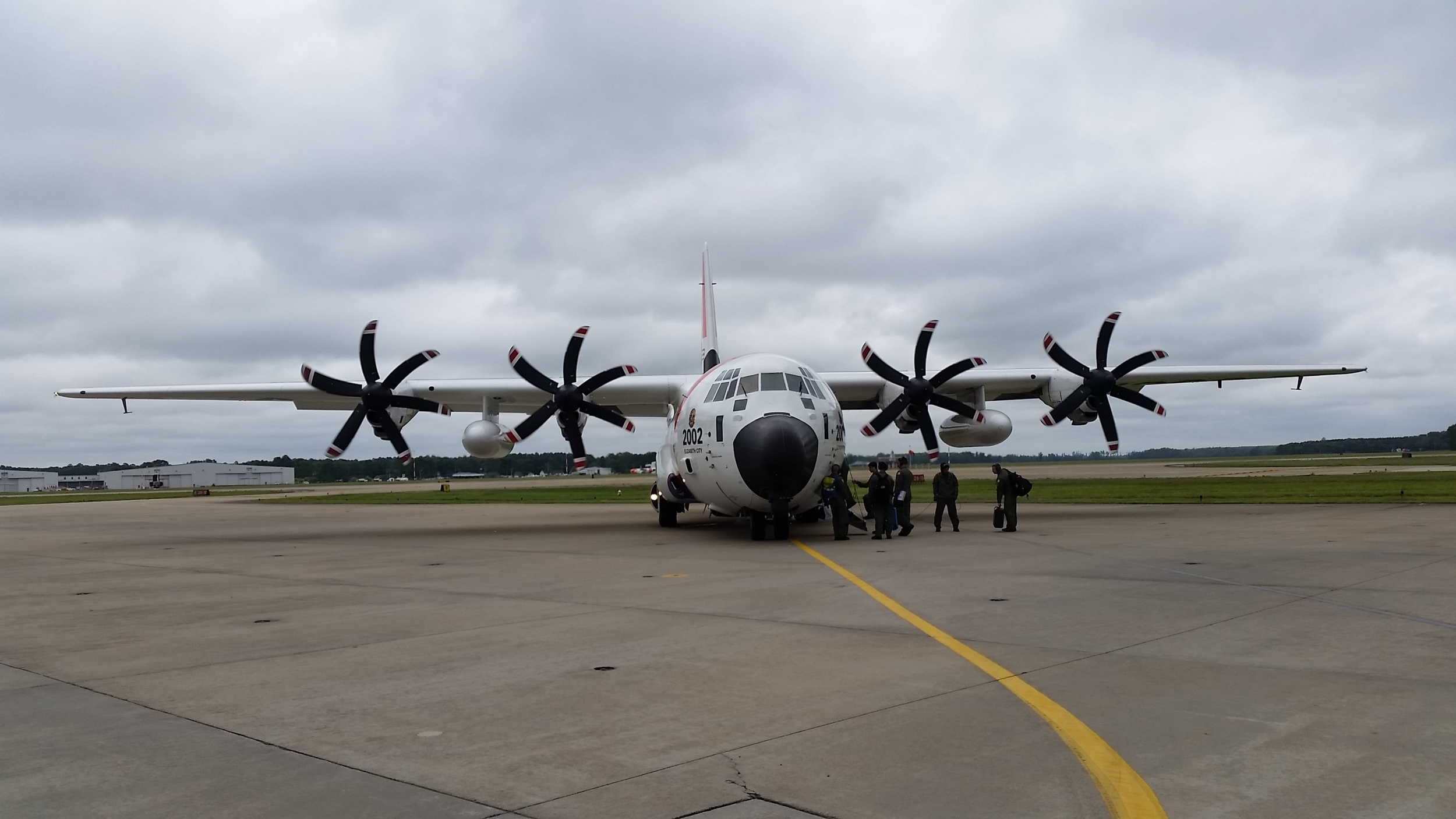 Cadets from the United States Coast Guard Academy board a HC-130J Hercules for an introduction flight