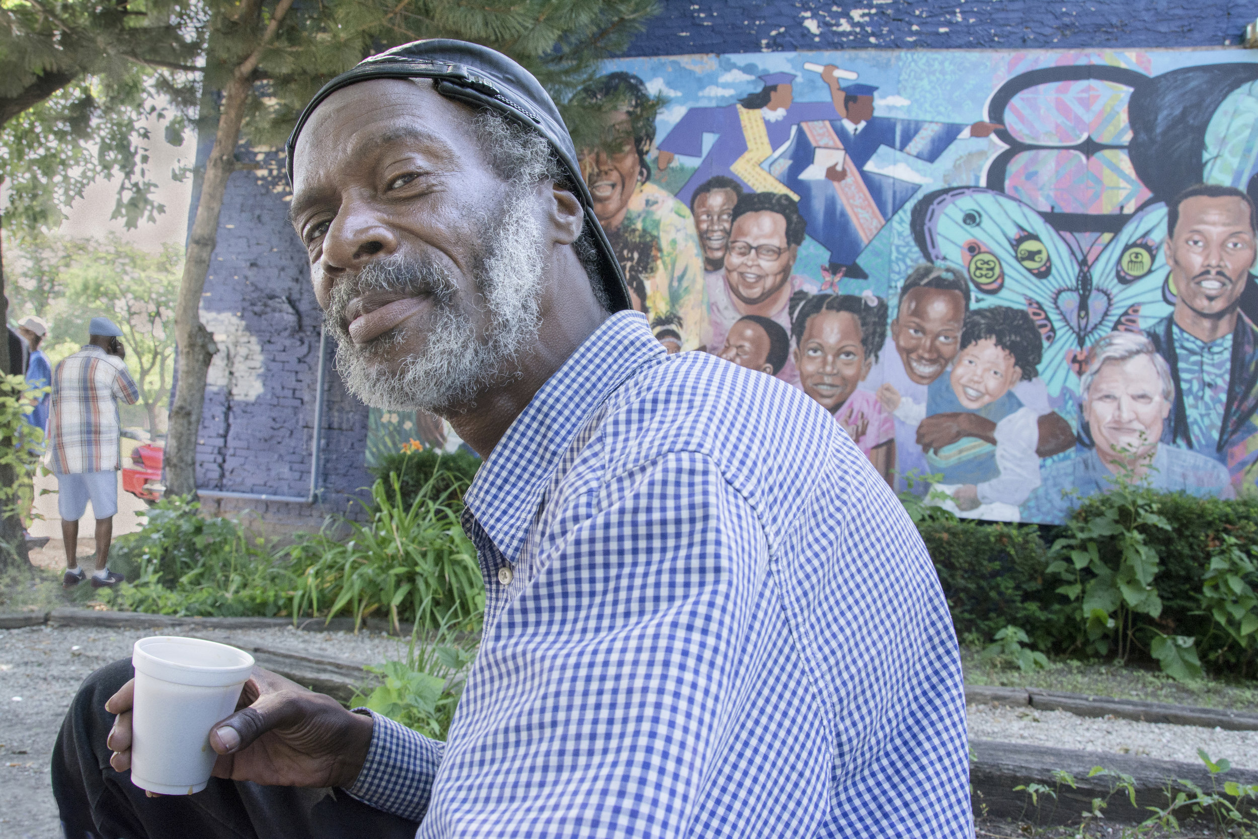 """Most mornings, Troy visits this little neighborhood garden and drinks his coffee. He said, """"That mural up there is a tribute to the two women who were murdered in this neighborhood 30 years ago. The others pictured are people who helped improve our neighborhoods."""" Milwaukee's violent crime rate has been among the highest among large cities. In 2014, there were 8,864 violent crimes, according to the FBI figures."""