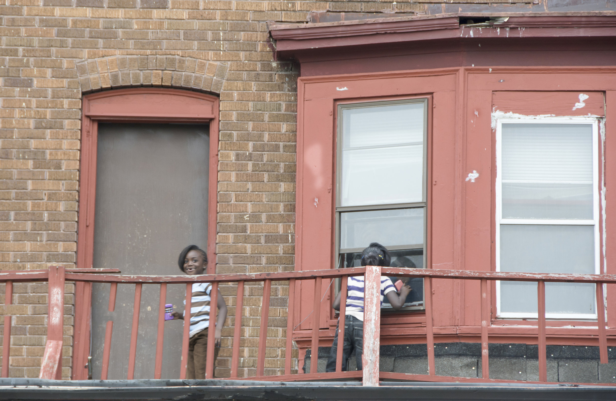These little girls seemed to confine their playtime from upstairs porch and into apartment. It's a two story drop to the street. There is no lawn.