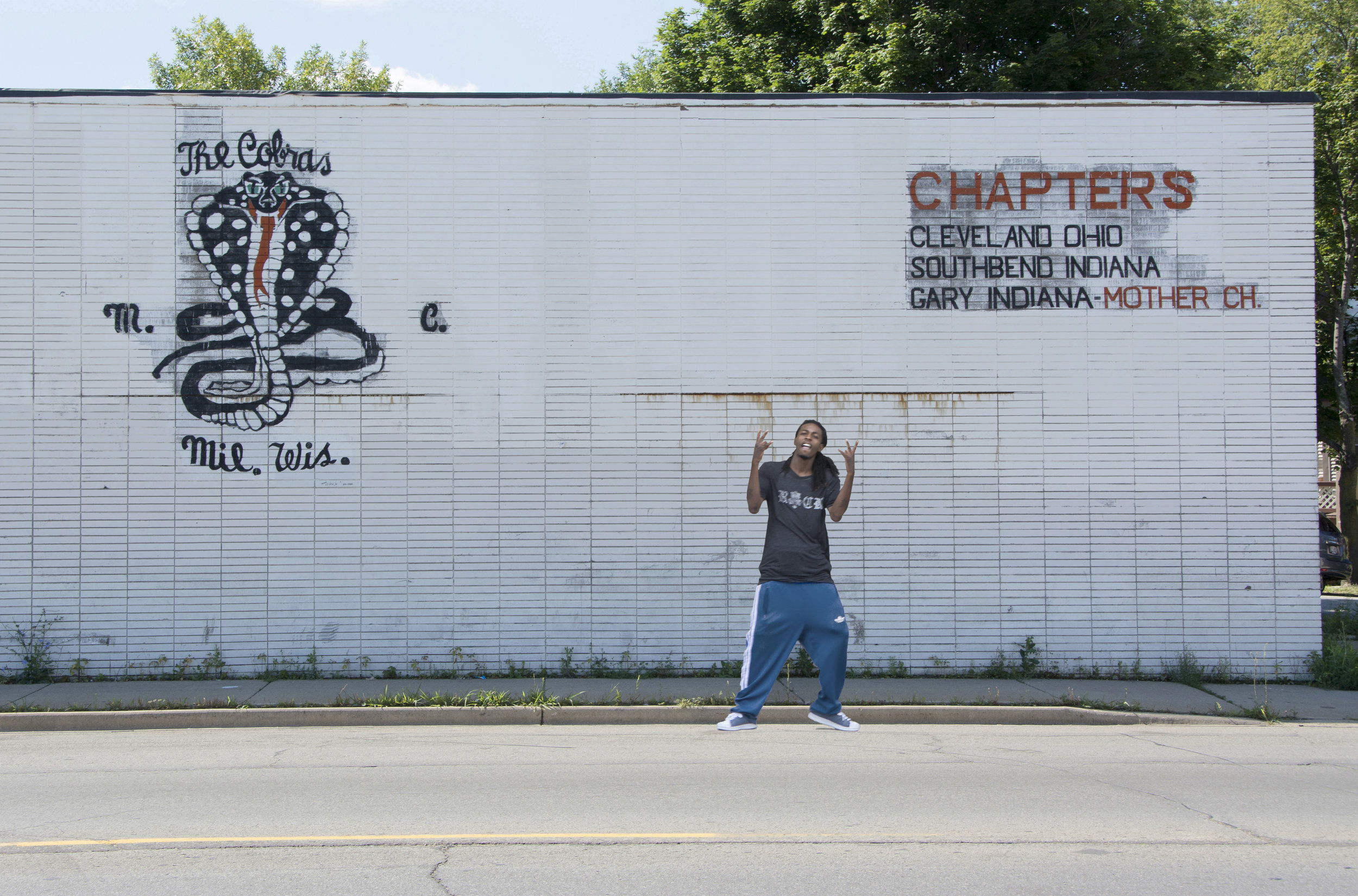 I asked this gang member to pose in front of the deserted Cobras building on North Avenue. He called me a motherfucker before I had a chance to explain. Finally, he posed but did it his way.