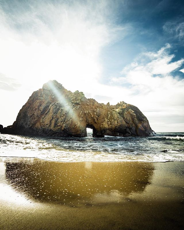 🌊 California moments... • A roadtrip down the PCH in California is one of those things I tell everyone I know to do once in their lives. Why? It's got everything. This shot was right in the middle of the highway, at Pfeifer Beach in Big Sur, a keyhole formation in a rock on a beach with purple sand. Something out of this world.