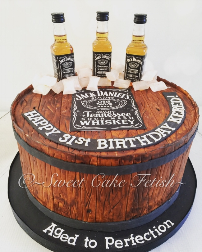 "This week we had a special order for a ""Mans Man cake"" :) The Birthday boy is a huge Jack Daniels fan so of course we had to make that the highlight of his Birthday cake. The cake was to be a barrel which we hand painted ourselves! All in all it was a huge success. :)"