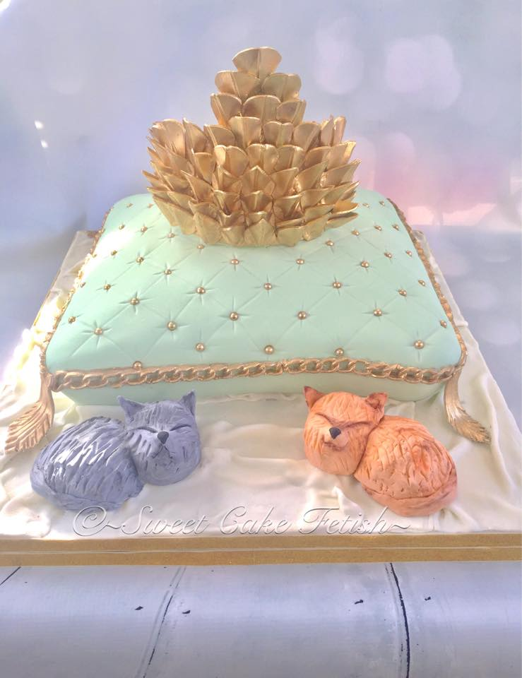 """This week we had a unique baby shower cake. The theme for the baby shower cake was Dragon Princess based on the famous TV show """"Game of Thrones"""".  The mom to be wanted a beautiful pillow cake with the princess crown on top! The cake also featured two gumpaste kitties which were made the same color as their actual cats.  Definitely a fun cake to make!"""